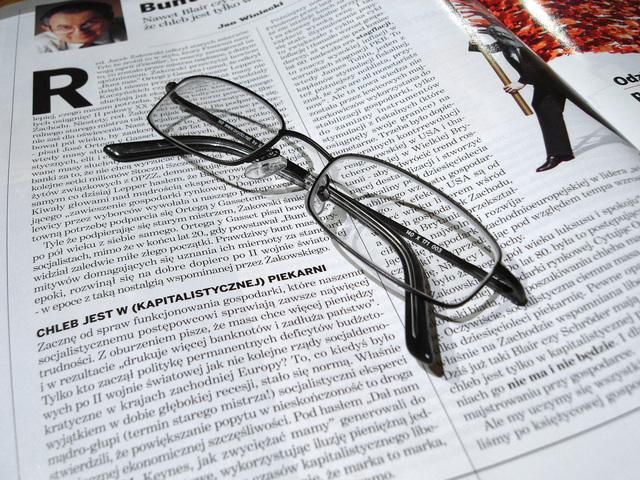 brýle na čtení položené na novinách